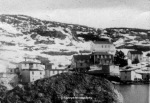 black and white photograph ofresettled community of bay du nord. A large boulder is seen in the foreground, white two-story houses in the middle ground and a snow-covered hillside in the background.