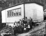 A group of school children of various ages with their male teacher standing in front of a one room white clapboard school house. Photo was taken around 1945.