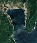 Google map of a coastal harbour showing terrain and green vegetation surrounding the water on three sides.