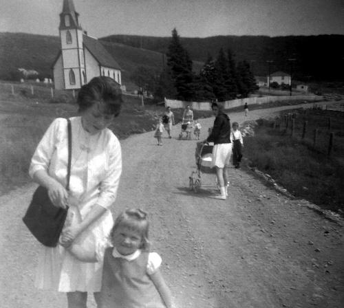 Women and children walking along a gravel road.